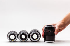 Man's hand adjusts a photographic lens. A collection of expensive toys for adults Stock Photography