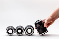 Man's hand adjusts a photographic lens. A collection of expensive toys for adults Royalty Free Stock Photography