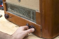 Man`s hand adjusts the potentiometer scale in the old vintage radio tube. The man`s hand adjusts the potentiometer scale in the old vintage radio tube stock photo