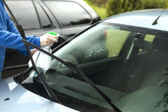 Man`s hand applies liquid to clean the windshield of the car window. The man`s hand applies liquid to clean the windshield of the car window Stock Photos