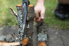 Man`s hand with an ax chops a log. Ax in the log stock photography