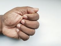 Clenched fist of an African-American person& x27;s hand on a white background stock photo