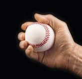 Man's hand with a baseball ball. On a black background Stock Photos