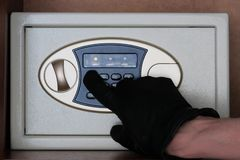A man in black gloves enters a security code on the safe. The thief hacks electronic safe in the office or at home. Theft. stock photo