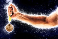 Man`s hand in a blue fire is holding gold medal. Winner in a competition. Man`s hand in a blue fire is holding gold medal on a dark background. Winner in a Stock Images