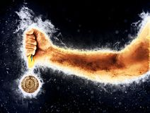 Man`s hand in a blue fire is holding gold medal. Winner in a competition. Man`s hand in a blue fire is holding gold medal on a dark background. Winner in a Stock Photo