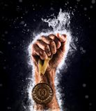 Man`s hand in a blue fire is holding up gold medal. Winner in a competition. Man`s hand in a blue fire is holding up gold medal on a dark background. Winner in Royalty Free Stock Photos