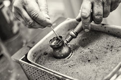A man's hand brewed Turkish coffee. Turkish coffee pots jezve. Drink brewed on the sand Royalty Free Stock Photography