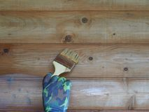 A man`s hand with a brush to paint a wooden wall. stock photo