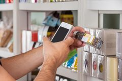 Man's Hand With Cellphone Scanning Product Stock Photo