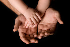 Man's hand and children's foot Stock Photos