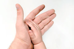 Man's hand and children's foot Royalty Free Stock Photography