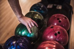 Man playing bowling. Man`s hand choosing a bowling ball ready to play with it Royalty Free Stock Photography