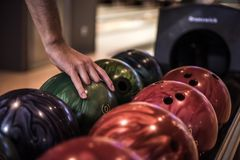Man playing bowling. Man`s hand choosing a bowling ball ready to play with it Royalty Free Stock Images