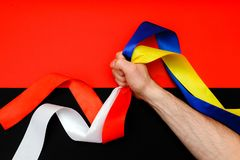 Red blue white yellow black conflict between Ukraine Poland two flag top view hand right sector confrontation. The man`s hand clamps in the fist the symbols of Royalty Free Stock Photography