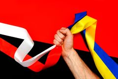 Red blue white yellow black conflict between Ukraine Poland two flag top view hand right sector confrontation. The man`s hand clamps in the fist the symbols of Stock Image