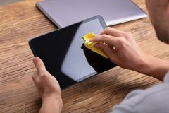 Man`s Hand Cleaning Digital Tablet Screen. With Soft Yellow Cloth stock photos