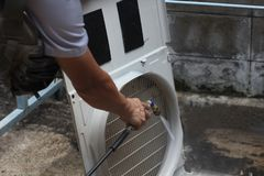 A man`s hand is clearing the air conditioner. stock photo