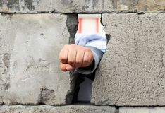 The man`s hand squeezed into a fist smashes through the wall of gray concrete blocks. Symbol of struggle, victory and liberation stock photography