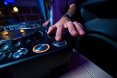 The man`s hand with the clock presses the button of the DJ keypa royalty free stock photo