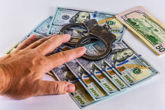 Man's hand covers the handcuffs and US dollars Royalty Free Stock Photo