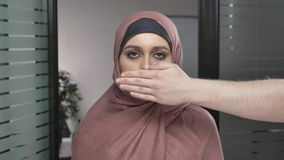Man`s hand covers a woman`s mouth. Arab woman in pink hijab. Problem, infringement, bullying. Looks at the camera. Man`s hand covers a woman`s mouth. Arab woman stock video footage