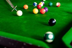 Man`s hand and Cue arm playing snooker game or preparing aiming to shoot pool balls on a green billiard table royalty free stock image