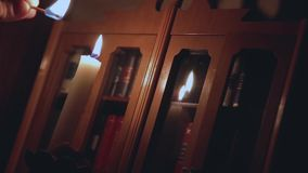 Man`s hand in the dark, lights a match to the wick of the old candle. HD 1920x1080 stock video