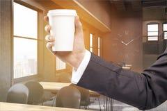 Man& x27; s-Hand in der sonnenbeschienen Kaffeestube mit Uhren Lizenzfreie Stockbilder