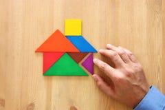 man& x27; s-Hand, die auf das Haus gemacht vom Tangrampuzzlespiel über Holztisch zeigt stockbilder