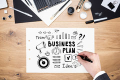 Man s hand drawing black business plan on paper. Top view of a businessman s hand drawing a business plan sketch on paper. Concept of a strategy in business stock photography
