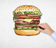 A man's hand is drawing a colourful burger. A concept of fast food. Stock Images