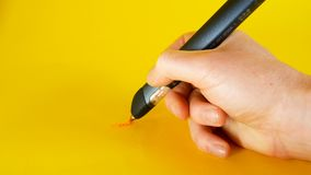 A man`s hand draws with a 3d printer pen on a yellow background, footage ideal for topics such as innovation, technology. Concept stock video footage