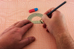 Man`s hand draws a diagram on a sheet of graph paper Royalty Free Stock Photo