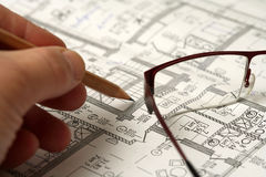 Man's hand draws a pencil business plan draft. With glasses Stock Photos