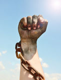 Man`s hand is encased in an iron rusty chain Stock Photo