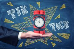 Man`s hand facing up holding dynamite bundle with time bomb on blackboard background with chalk words `tick tock`. Time is ticking away. Business waits for no royalty free stock image