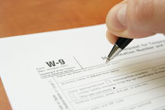 Man's hand filling tax forms Stock Photo