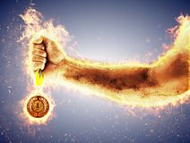 Man`s hand in a fire is holding gold medal. Winner in a competition. Man`s hand in a fire is holding gold medal on a blue background. Winner in a competition Stock Photo
