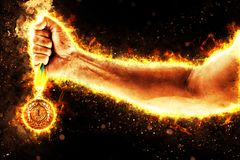 Man`s hand in a fire is holding up gold medal. Winner in a competition. Man`s hand in a fire is holding up gold medal on a dark background. Winner in a Royalty Free Stock Photography