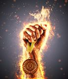 Man`s hand in a fire is holding up gold medal. Winner in a competition. Man`s hand in a fire is holding up gold medal on a dark background. Winner in a Royalty Free Stock Photos