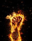 Man`s hand in a fire is holding up gold medal. Winner in a competition. Man`s hand in a fire is holding up gold medal on a dark background. Winner in a Royalty Free Stock Image