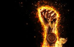 Man`s hand in a fire is holding up gold medal. Winner in a competition. Man`s hand in a fire is holding up gold medal on a dark background. Winner in a Stock Images