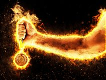 Man`s hand in a fire is holding up gold medal. Winner in a competition. Man`s hand in a fire is holding up gold medal on a dark background. Winner in a Royalty Free Stock Images