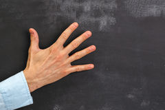 Man's hand gesturing on dark chalkboard with copy-space Royalty Free Stock Images