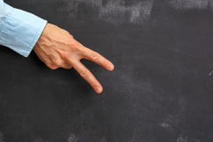 Man's hand gesturing on dark chalkboard with copy-space Stock Image