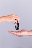 Man's hand gives car remote to another hand Royalty Free Stock Image
