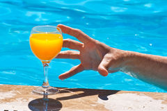 Man's hand and glass with orange juice Stock Images