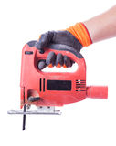 Man's hand in a glove holds a working jig saw Royalty Free Stock Photos