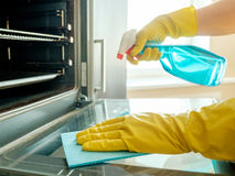 Man`s hand in glove with rag cleaning oven stock photo